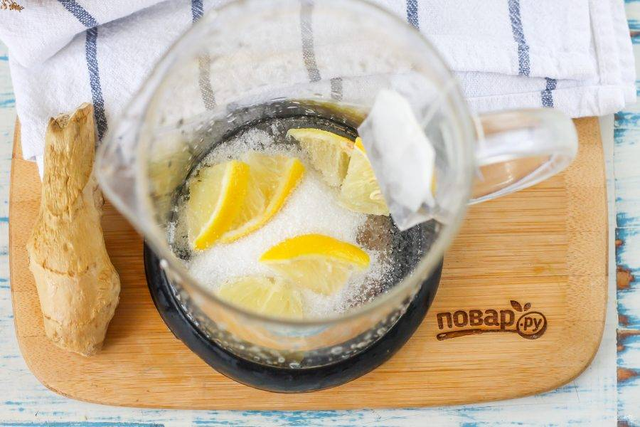 Всыпьте сахар в заварочный чайник, часть лимона нарежьте ломтиками, удалите из них семена и добавьте в чайник. Если будете использовать цветочный мед вместо сахара, то просто подайте его в отдельной пиале, чтобы гости выкладывали его в слегка остывший чай, иначе мед потеряет свои полезные качества, залитый кипятком.