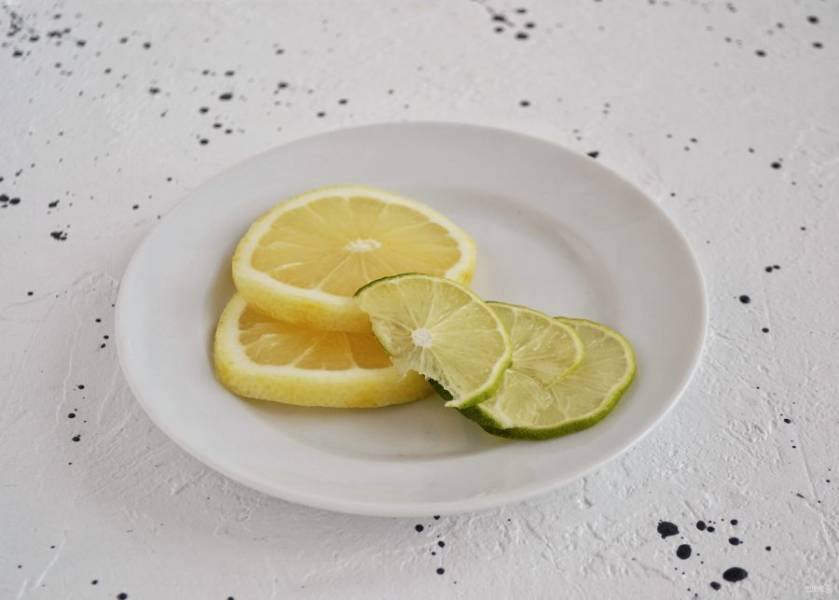 Нарежьте лимон и лайм на кружочки. Добавьте их в напиток.