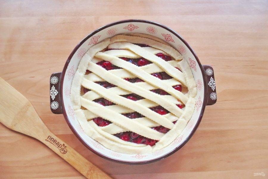 Вторую часть теста раскатайте, нарежьте полоски и выложите на вишневую начинку крест на крест.