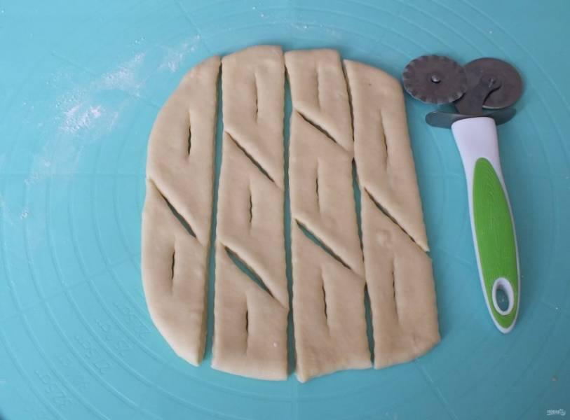 Нарежьте полосы и разрежьте на небольшие кусочки, в середине сделайте прорезь.