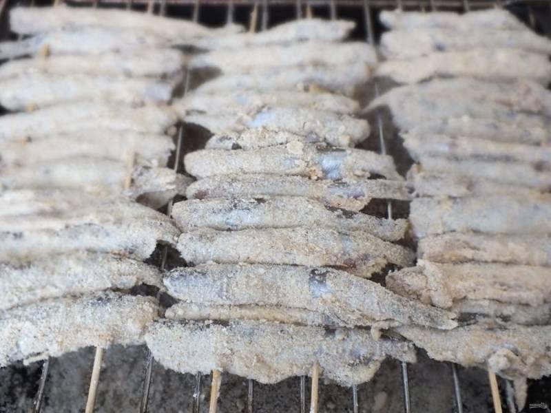 Возьмите две длинные шпажки. Каждую рыбку нанизайте на шпажки. На противень насыпьте соль. Включите духовку на 180 градусов. Переложите насаженную мойву на решетку, решетку поставьте на противень с солью. Запекайте в духовке 20 минут.