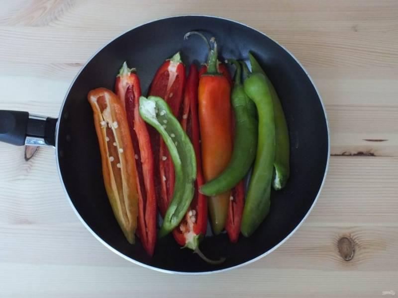 Перец разрежьте пополам, удалите семена. В сковороде разогрейте масло и положите обжариваться перцы.