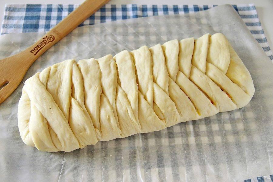 Поочередно переплетая полоски теста сформируйте косичку. Оставьте готовую косичку в теплом месте на 20-30 минут для подъема, после чего смажьте желтком и выпекайте при температуре 200 градусов около 30 минут.