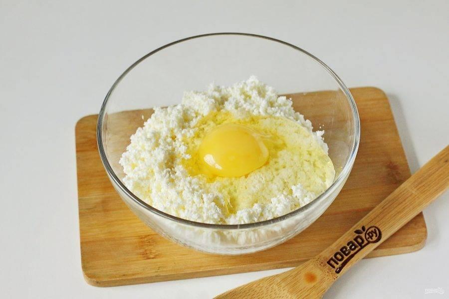 Переложите творог в глубокую миску и добавьте яйцо.