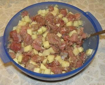Итак, приступим к готовке, первым нашим шагом будет подготовка продуктов. Моем картошку, чистим ее и режем на кусочки, мелкие кубики. Точно также режем мясо, мясо можно взять любое, это не принципиально, фарш, кстати, тоже очень хорошо подойдет. Если не хотите резать картошку кубиками, можно сделать картофельное пюре. Теперь все это соединяем в какой-нибудь мисочке, туда добавляем измельченный лук, солим, перчим и хорошенько перемешиваем все содержимое миски.