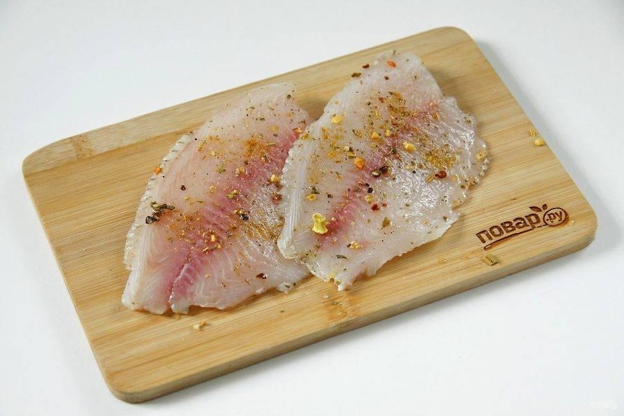 Рыбу разморозьте, натрите солью и специями, сбрызните соком лимона и оставьте мариноваться минимум на 20-30 минут.