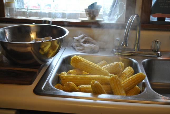 4. Затем кукурузу надо выложить в чистую раковину или другую емкость и остудить. Воду, в которой варились початки, не сливаем!