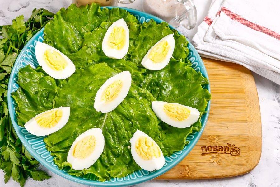 Куриные яйца очистите от скорлупы, промойте в воде и нарежьте четвертинками. Выложите их на листья салата.