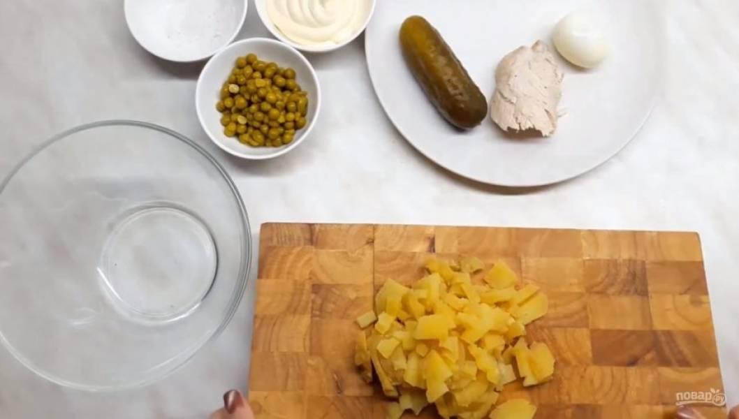 1. Отварите мясо птицы. Картофель отварите заранее и дайте ему остыть, чтобы его можно было аккуратно нарезать. Нарежьте картофель кубиками со стороной примерно 5 мм. Сварите яйца вкрутую.