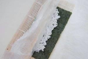 Начинайте закручивать ролл, нажимая равномерно сверху. Не покрытые рисом нори смажьте водой, чтобы улучшить клейкость.
