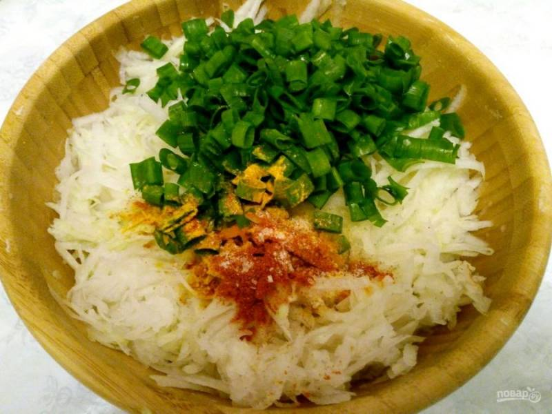 Приготовьте начинку из натёртой на крупной тёрке капусты, зелёного лука, щепотки соли, паприки и куркумы.