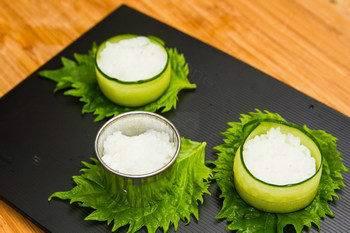 На сервировочное блюдо поместите листья салата. Полоски огурца скрепите в виде чашек. Внутрь положите комочки риса.