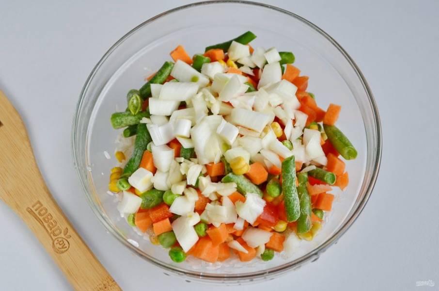 Добавьте к рису овощной микс, порезанный кубиками лук и чеснок. Перемешайте.