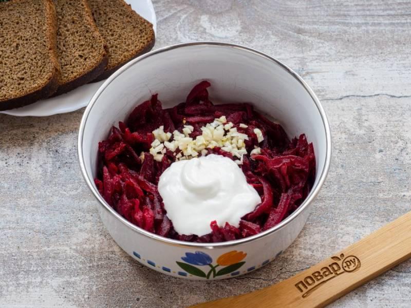 Натрите свеклу на терке, добавьте рубленый мелко чеснок и сметану. Перемешайте и посолите по вкусу.