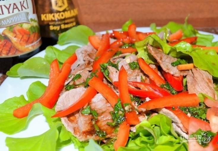 Листья салата промойте и обсушите. Выложите их на широкое блюдо. Следом выложите говядину, чередуя её с перцем и зеленью. Обильно полейте закуску соусом, а также присыпьте кунжутом. Приятного аппетита!
