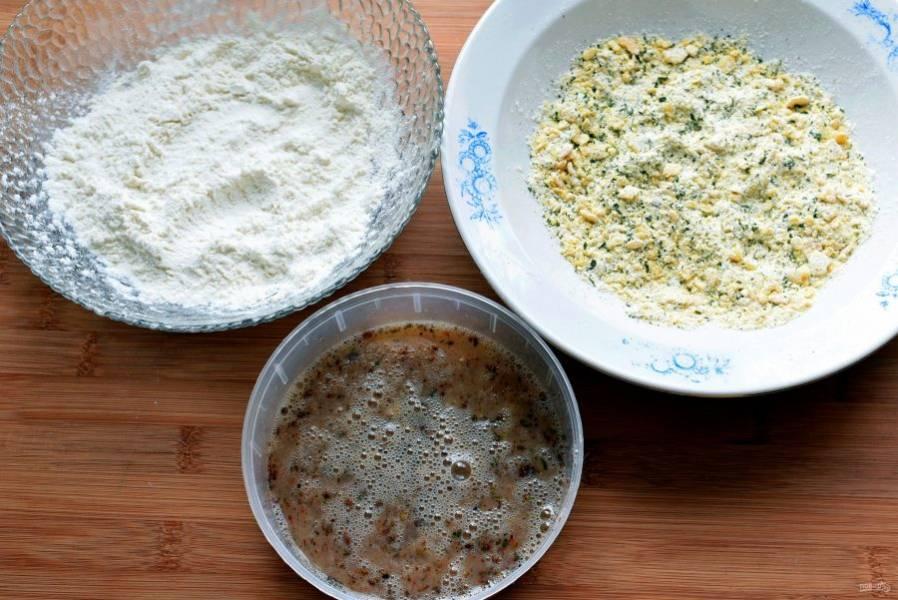 Приготовьте панировочную линию. В одной миске соедините муку, соль и перец. Во вторую миску разбейте яйца, добавьте соль, смесь мексиканских пряностей и растопленное сливочное масло. В третьей миске смешайте измельченные кукурузные хлопья, сушеную зелень кинзы или петрушки.