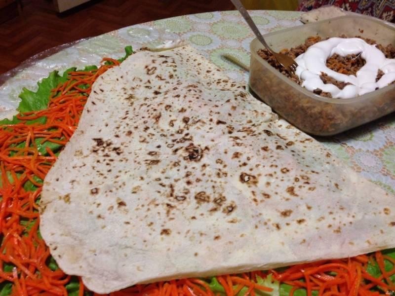 Печенку перемешайте майонезом, выложите поверх корейской морковки, аккуратно и равномерно распределите.