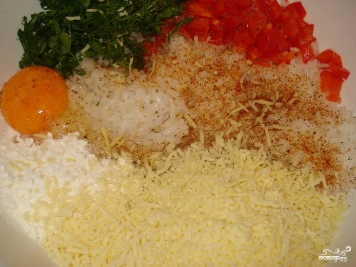 Выкладываем в глубокую миску предварительно отваренный рис, добавляем натертый на крупной терке сыр, нарезанный мелко красный перец, измельченную зелень, муку и яичный желток. Солим и посыпаем перцем, тщательно все перемешиваем до образования однородной массы.
