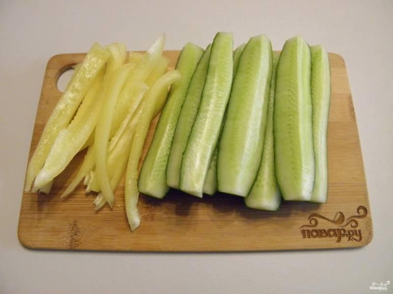 Овощи все тщательно вымойте. У огурцов срежьте попки. Сами же огурчики порежьте на 4-6 частей вдоль. Болгарский перец освободите от семян, промойте внутри и порежьте тонкими полосочками вдоль.