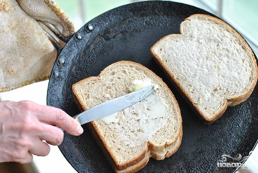 6. Смазать размягченным сливочным маслом одну сторону сэндвича и выложить на сковороду смазанной стороной вниз, обжарить до золотисто-коричневого цвета, смазать сливочным маслом другую сторону и перевернуть. Жарить до готовности.