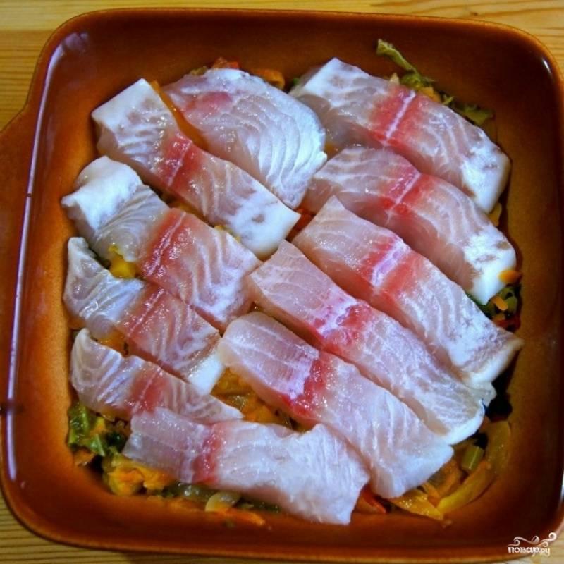 На овощи выкладываем кусочки филе пангасиуса. Солим, перчим, посыпаем желаемыми специями.