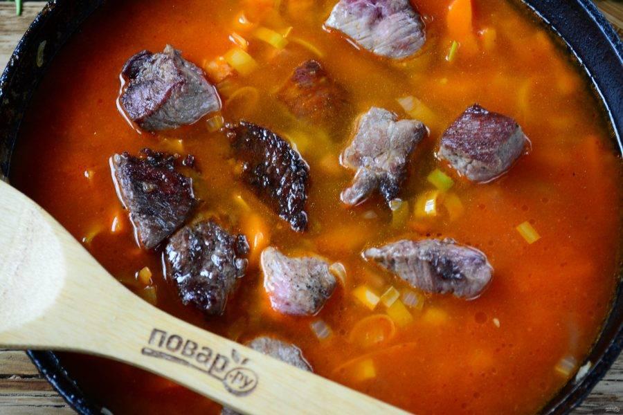 Затем влейте примерно 750 мл воды или бульона, верните в сковороду обжаренное мясо, добавьте соль, перец, сахар, лавровый лист.