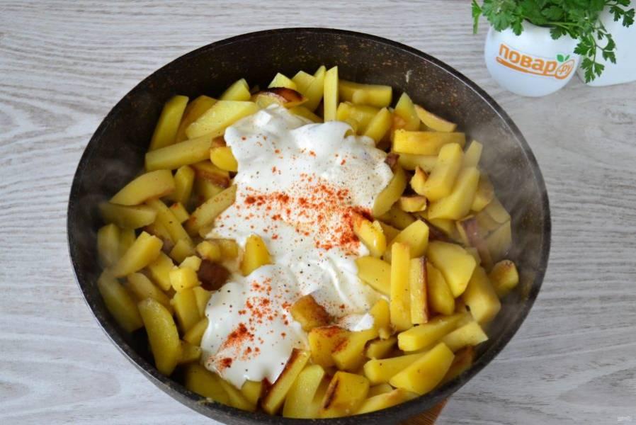Когда картофель будет наполовину готов (время зависит от сорта картофеля), добавьте в сковороду сметану, соль, перец и паприку.