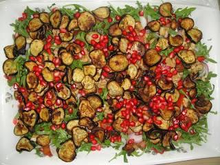 На блюдо выложите рукколу, на нее - слой помидоров и лука, затем баклажаны. Посыпьте салат тертыми орехами и зернами граната. Полейте соусом из граната с маслом. Специи добавьте по вкусу.