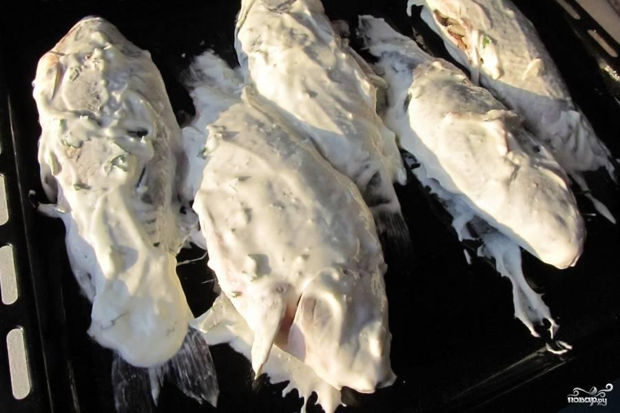 В чашке смешайте сметану и приправы. Выложите рыбу на противень и смажьте сметаной. Не жалейте сметаны, пусть она покрывает всю рыбу.