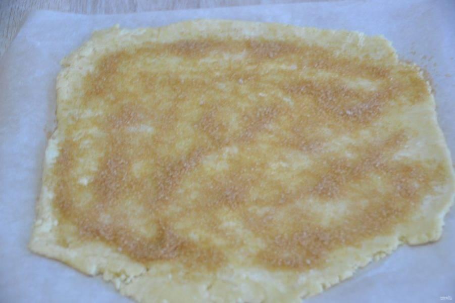 Раскатайте тесто на листе для выпечки. Для того, чтобы тесто лучше раскатывалось, сверху прикройте еще одним листом пергамента. Присыпьте поверхность теста коричневым сахаром.