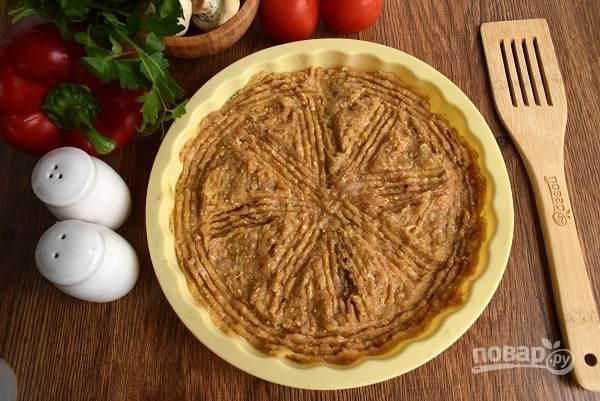 Выложите мясной фарш в силиконовую круглую форму для запекания, разровняйте. Или можете выложить в виде круглой лепешки на противень, выстланный пергаментом для выпечки. Запекайте в разогретой до 180°C духовке в течение 15 минут.