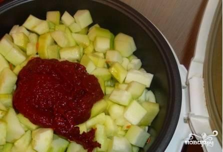 Очищенные кабачки нарежьте мелкими кубиками и опустите в мультиварку. Также добавьте томатную пасту, соль, сахар, специи и полстакана растительного масла. Ставьте готовиться в режиме «Выпечка» в течение 60 минут. Периодически помешивайте овощи.