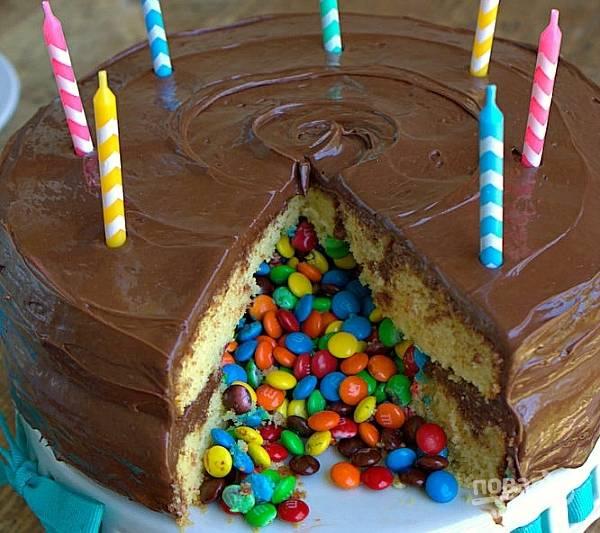 Уберите торт на пару часов в холодильник. Затем украсьте его свечками. Подавайте, нарезав на кусочки и добавив ещё конфет для украшения по желанию. Счастливого праздника!
