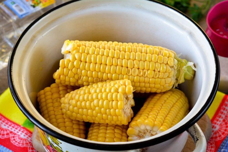 Почистите кукурузу и сложите початки в кастрюлю. Если початки крупные - разломайте их пополам.