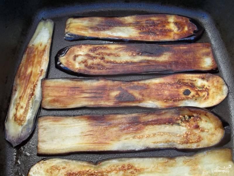 Баклажаны нарежьте на тонкие продольные пластины. Разогрейте в сковороде масло, выложите нарезанные баклажаны, накройте крышкой и жарьте 4 минуты на среднем огне. Затем крышку снимите, баклажаны переверните и жарьте еще 4 минуты без крышки.