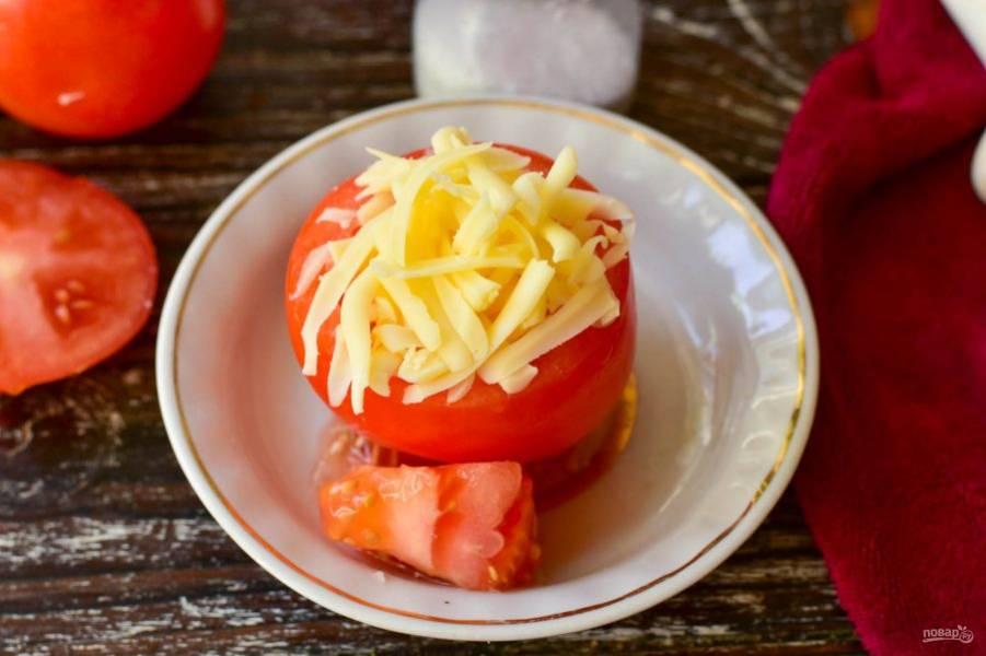 Выложите сыр внутрь помидоров.