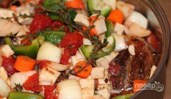 Затем в кастрюлю выложите мясо, все овощи, 10 веточек тимьяна, лавровый лист и помидоры. Влейте масло со сковороды и воду. Доведите ингредиенты до кипения.