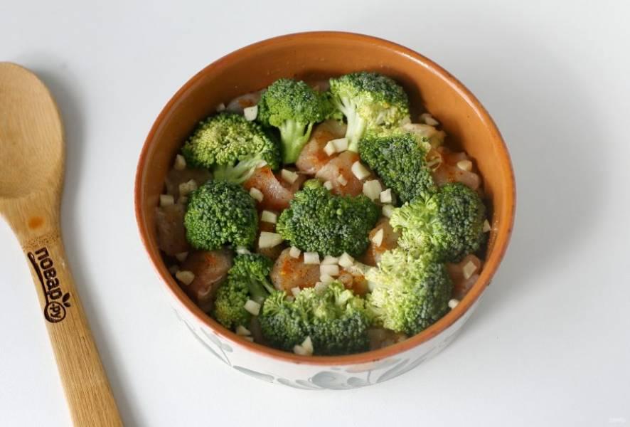 Брокколи разберите на соцветия, промойте и выложите рядом с грудкой. Посыпьте брокколи солью и молотым перцем.