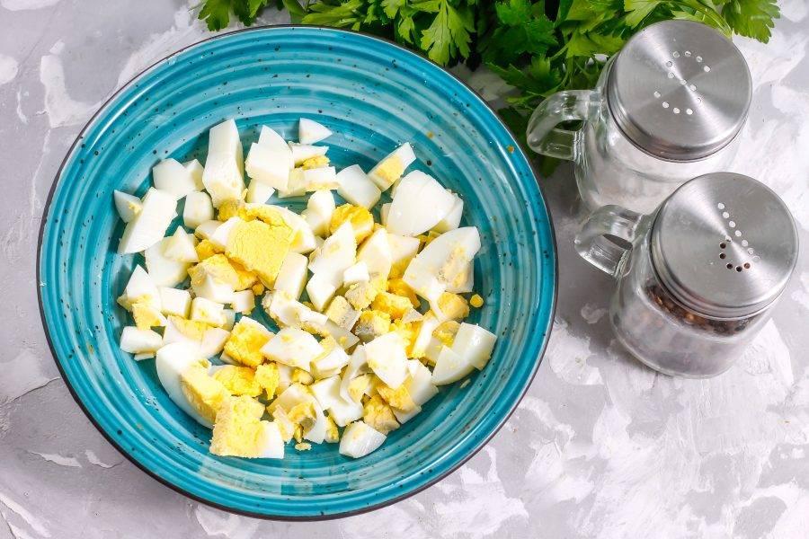 Заранее отварите и остудите куриные яйца. Очистите от скорлупы, промойте в воде и нарежьте кубиками. Всыпьте в миску или салатник.