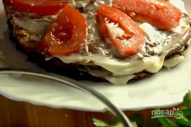 7. Можно собирать торт. Печеночный блин смажьте майонезом, на него положите омлет, затем — майонез и слой помидоров. И так чередуйте до конца.