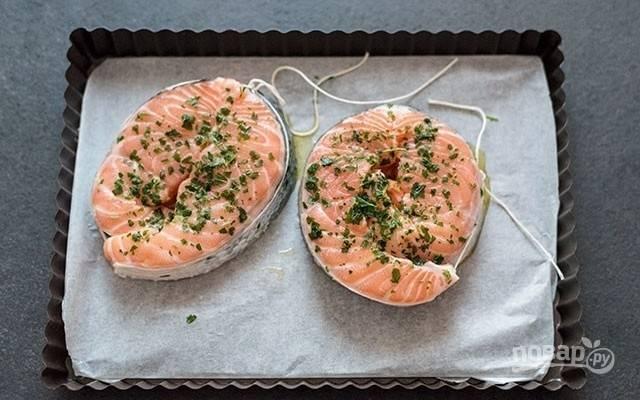 2.Положите рыбу на противень, покрытый пергаментом, и каждый ломтик рыбы сдобрите измельченным чесноком и петрушкой.