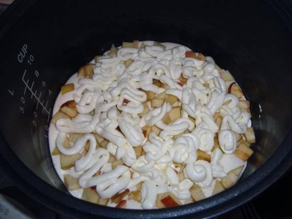 Берем чашу мультиварки, заливаем в нее половину теста. Разравниваем его, кладем на тесто нарезанные дольками яблоки. Оставляем про запас ровно столько, чтобы покрыть поверхность шарлотки. Сверху заливаем все творожной массой.