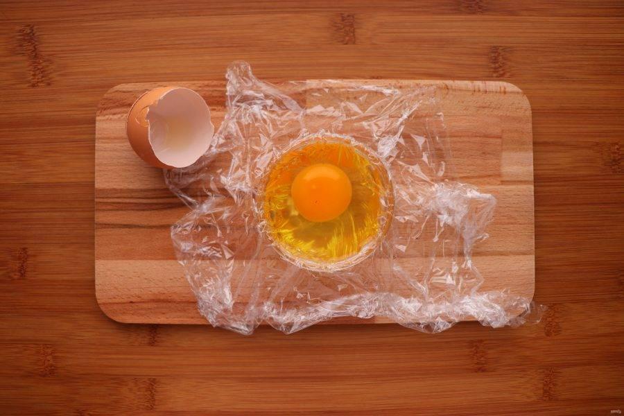 Аккуратно разбейте яйцо, не повредив желток.