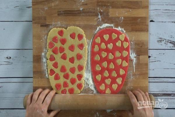 8.Вставьте сердечки одного цвета в пласт теста контрастного цвета. Излишки муки смахните кисточкой, а если необходимо, слегка смажьте тесто водой. По каждому пласту теста с сердечками пройдитесь скалкой.