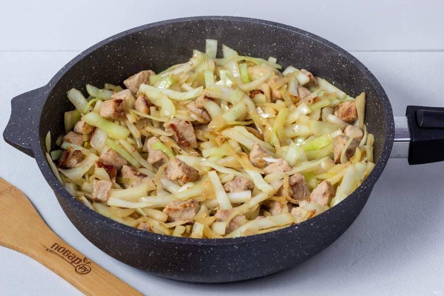 Затем добавьте нашинкованную капусту. Как только капуста схватится от жарки - накройте крышкой.