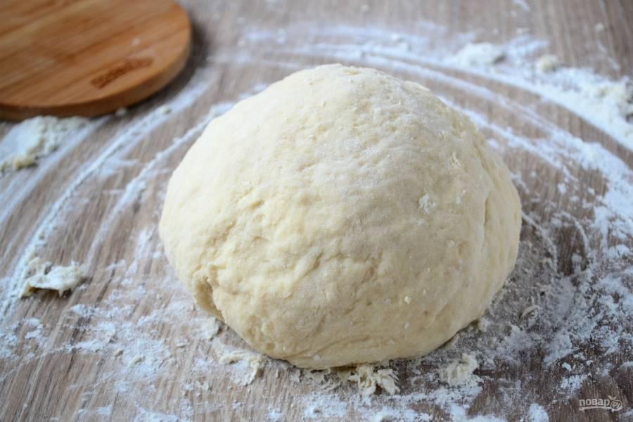 Когда месить станет сложнее, переложите тесто на рабочую поверхность и, подсыпая муку, замесите мягкое тесто. Оставьте его на 15-20 минут в теплом месте. А тем временем из холодильника достаньте сливочное масло. Дождитесь, чтобы оно размягчилось.