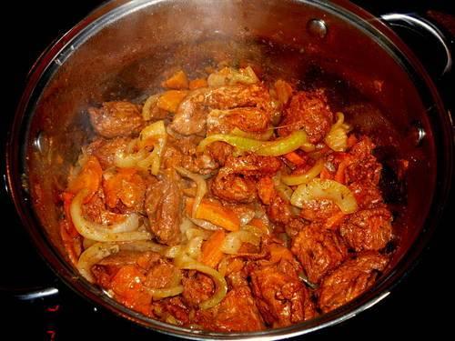 Растительное масло нагрелось, овощи под мясом начали обжариваться - перемешиваем мясо с овощами и даем ему немного обжариться.