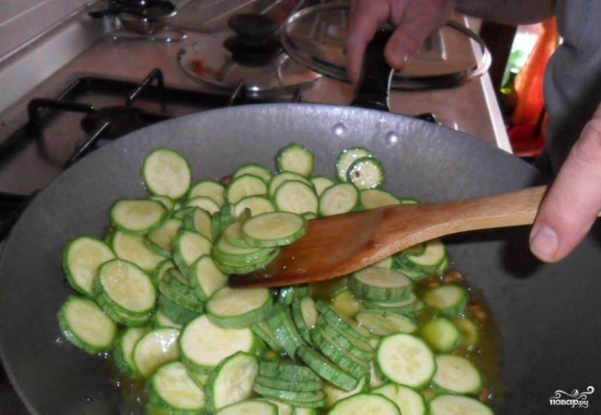 В сковородку вливаем масло и жарим кабачки, солим, перчим, добавляем мелко порубленный чеснок.