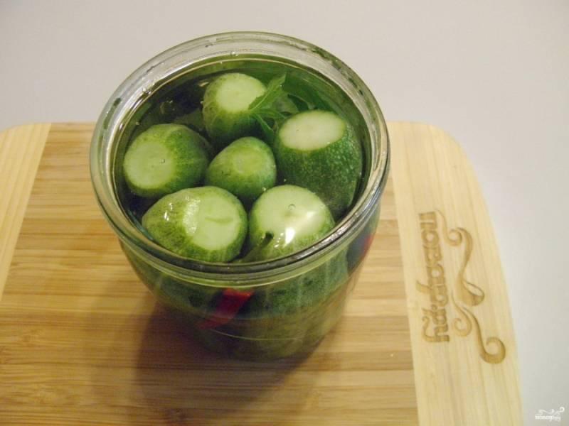 Из воды, соли, сахара и уксуса приготовьте маринад. Для этого воду доведите до кипения, растворите в ней соль и сахар, влейте уксус, а затем выключите огонь. Готовым маринадом залейте баночки с огурчиками. Поставьте баночку в горячую воду, стерилизуйте каждую по 5 минут. После баночки закатайте. Переверните их вверх дном и оставьте остывать. Всё.