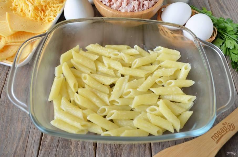 Готовые макароны откиньте на дуршлаг, смажьте сливочным маслом. Возьмите небольшой противень с высокими бортами или огнеупорную форму. На дно выложите тонкий слой макарон.